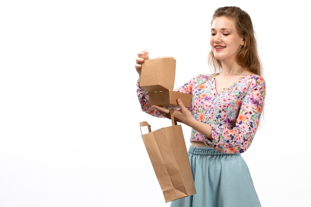A front view young attractive lady in colorful flower designed shirt and blue skirt brown package and box smiling on the white