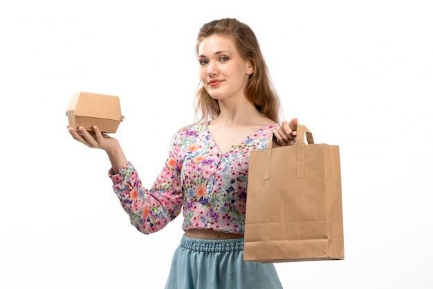 Una giovane signora attraente di vista frontale in camicia colorata fiore progettato e pacchetto blu gonna marrone e scatola sorridente sul bianco