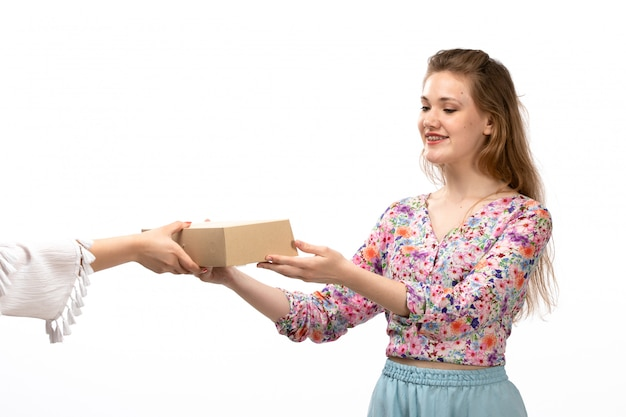 A front view young attractive lady in colorful flower designed shirt and blue skirt getting little package on the white
