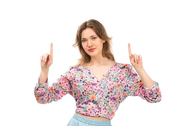 Una giovane signora attraente di vista frontale in camicia colorata del fiore progettata ed espressione blu della mano della gonna sul bianco