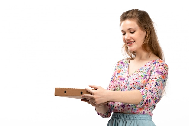 A front view young attractive lady in colorful flower designed shirt and blue skirt holding brown package smiling on the white