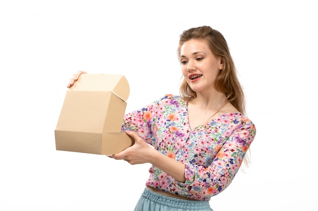 A front view young attractive lady in colorful flower designed shirt and blue skirt holding little package on the white