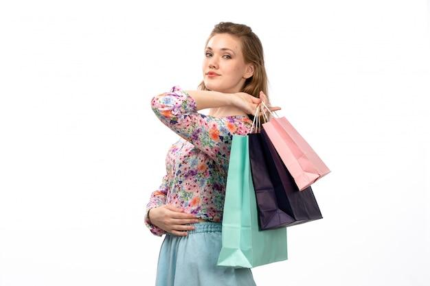 Una giovane signora attraente di vista frontale in camicia variopinta progettata fiore e pacchetti blu che tengono i pacchetti di acquisto sul bianco