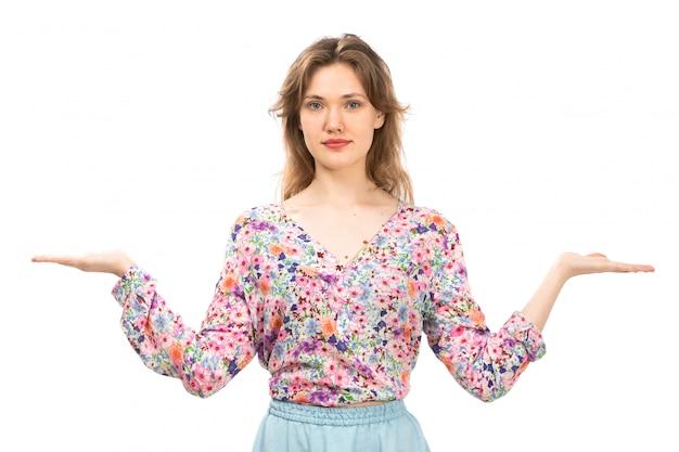 Una giovane signora attraente di vista frontale in camicia colorata fiore progettato e gonna blu in posa con le palme aperte sul bianco