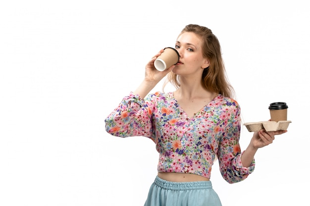 A front view young attractive lady in colorful shirt and blue skirt drinking coffee on the white