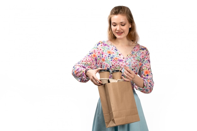 A front view young attractive lady in colorful shirt and blue skirt holding brown package with coffee on the white