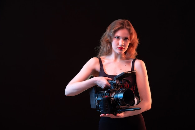 A front view young attractive lady in fire shirt and black trousers holding black video camera on the black background shot recording
