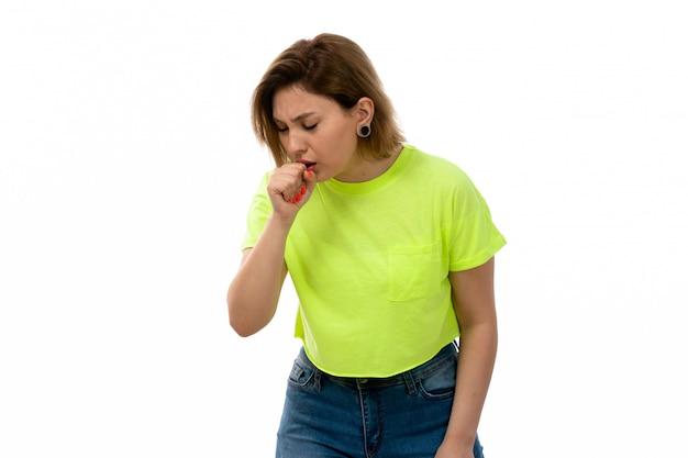 Una giovane signora attraente di vista frontale in camicia verde e blue jeans che tossiscono sul bianco