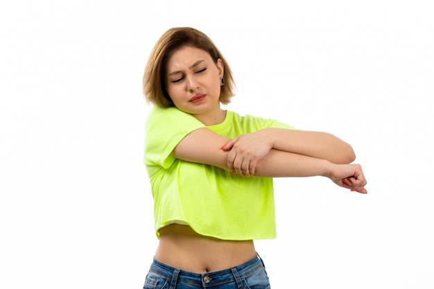 A front view young attractive lady in green shirt and blue jeans suffering from hand ache on the white