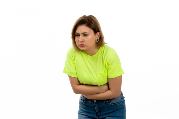 A front view young attractive lady in green shirt and blue jeans suffering from stomachache on the white