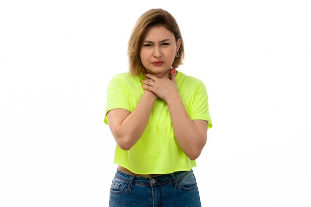 A front view young attractive lady in green shirt and blue jeans suffering from throat ache on the white