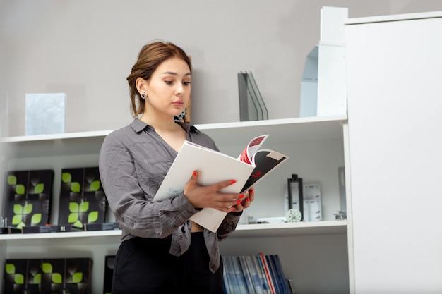 Una giovane donna attraente di vista frontale in camicia grigia e pantaloni neri guardando attraverso libri e riviste vicino stand con il libro di riviste in camera