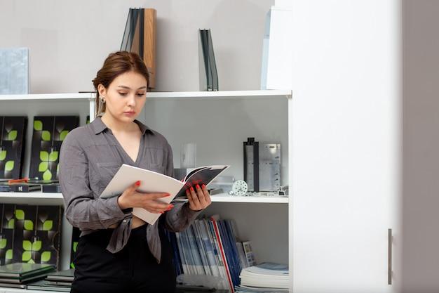 Una giovane donna attraente vista frontale in camicia grigia e pantaloni neri guardando attraverso i libri vicino stand con il libro di riviste in camera