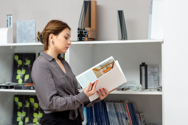 A front view young attractive lady in grey shirt and black trousers looking through books near stand with books room magazines book