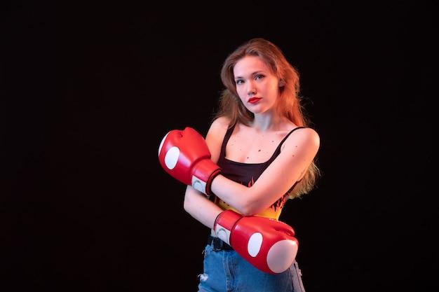 Una giovane signora attraente di vista frontale in guantoni da pugile rossi spara la camicia sull'addestramento nero di pugilato di sport del fondo