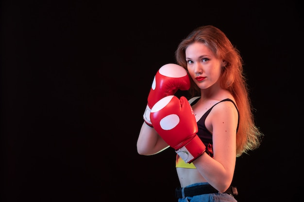 A front view young attractive lady in red boxing gloves fire shirt on the black background sport boxing training