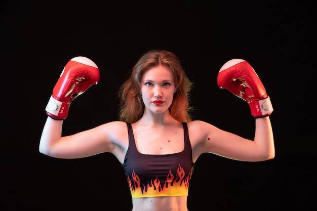 Una giovane signora attraente di vista frontale in guantoni da pugile rossi infila la camicia che flette sull'addestramento nero di pugilato di sport del fondo