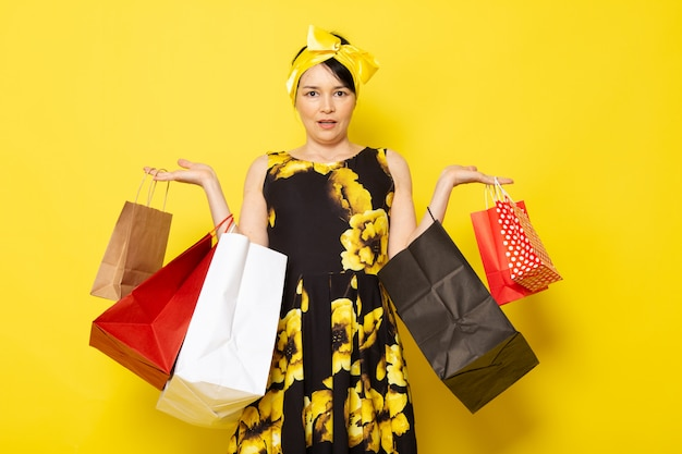 A front view young attractive lady in yellow-black flower designed dress with yellow bandage on head posing holding shopping packages on the yellow