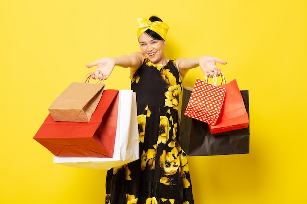 A front view young attractive lady in yellow-black flower designed dress with yellow bandage on head smiling holding shopping packages on the yellow