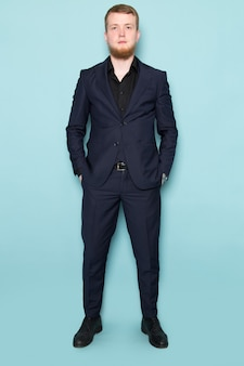 A front view young attractive male with beard in black dark classic modern suit on the blue space
