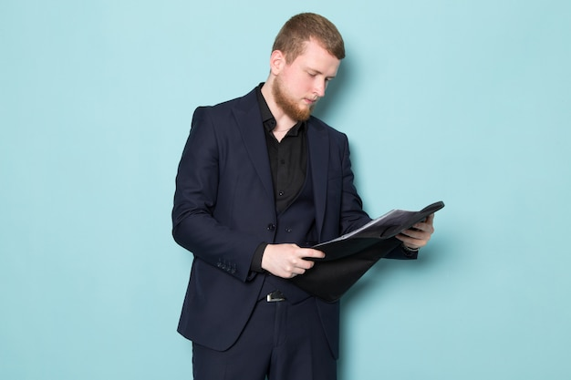 A front view young attractive male with beard in black dark classic modern suit holding black leather folder on the blue space