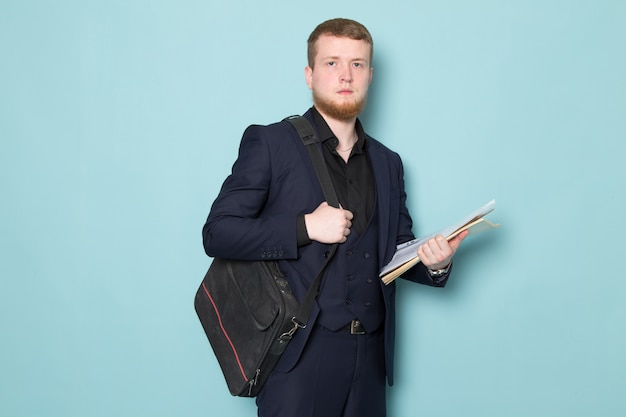 A front view young attractive male with beard in black dark classic modern suit holding files backpack on the blue space