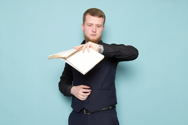 A front view young attractive male with beard in black dark classic modern suit holding files looking at his wrist watch on the blue space