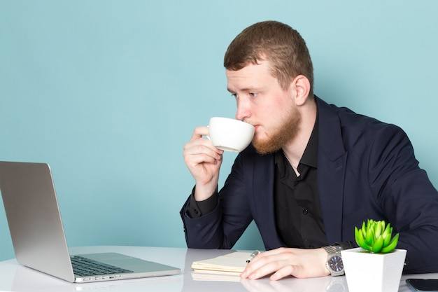 A front view young attractive male with beard in black dark classic modern suit using laptop drinking coffee on the blue space