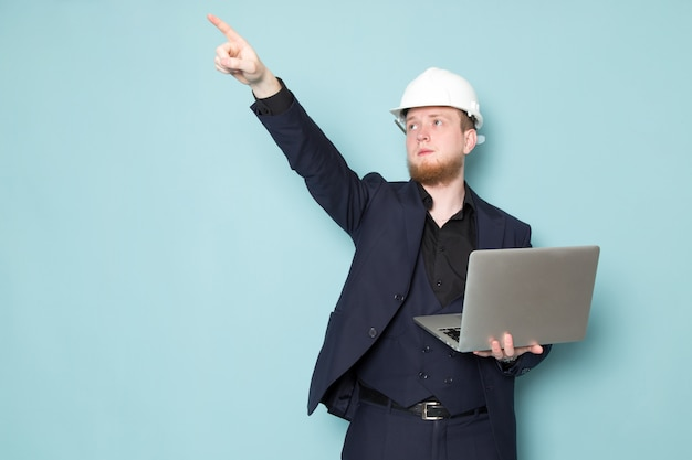 A front view young attractive male with beard in black dark classic modern suit white construction helmet using grey laptop on the blue space