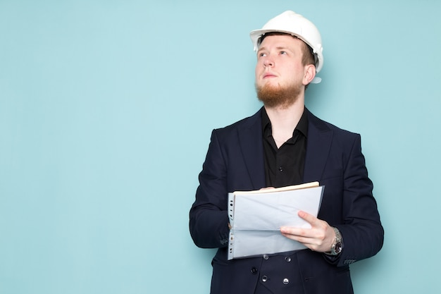 A front view young attractive male with beard in black dark classic modern suit in white construction helmet writing down notes on the blue space