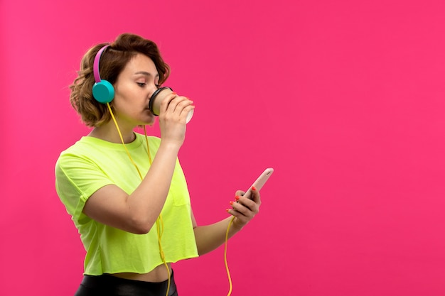 A front view young attractive woman in acid colored shirt black trousers in blue earphones listenign to music using her phone drinking coffee on the pink background young female youth