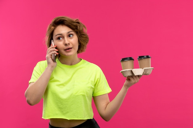 A front view young attractive woman in acid colored shirt black trousers talking on the phone holding coffee cups on the pink background young female technologies talking