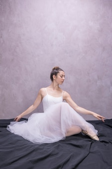 Front view young ballerina sitting