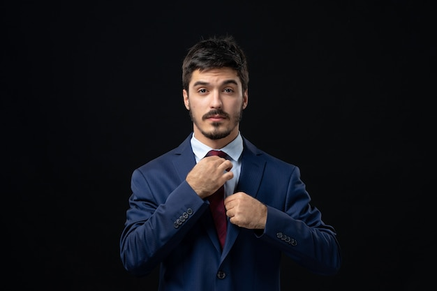 Front view of young bearded man in suit straightening his tie on dark wall