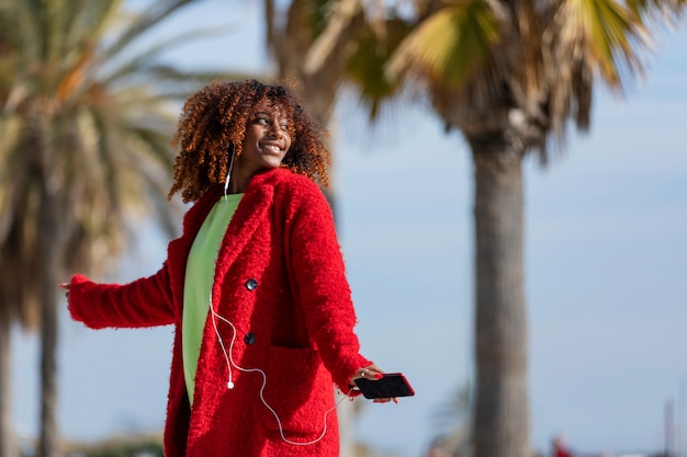 Front view of young beautiful curly african american woman dancing and listening music while looking away outdoors