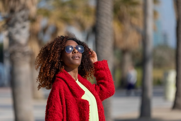 Front view of young beautiful curly afro woman wearing sunglasses and red jacket standing in a city street while touching hair and smiling in a sunny day
