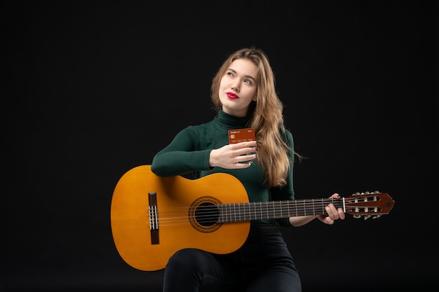 Front view of young beautiful dreamy musician girl holding guitar and bank card on dark