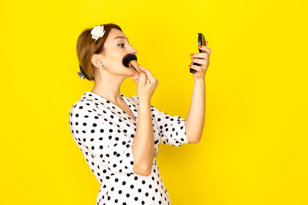 A front view young beautiful female in black and white polka dot dress doing make-up on yellow