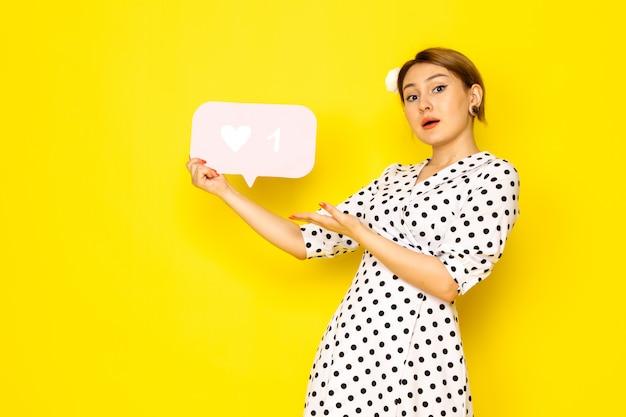 Una giovane bella femmina di vista frontale in vestito a pois in bianco e nero che tiene bianco come segno su giallo