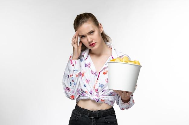 正面図若い美しい女性がジャガイモのcipsを食べて、白い表面で強調された映画を見て