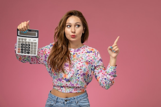 Front view young beautiful female in flower designed shirt and blue jeans holding calculator on pink background