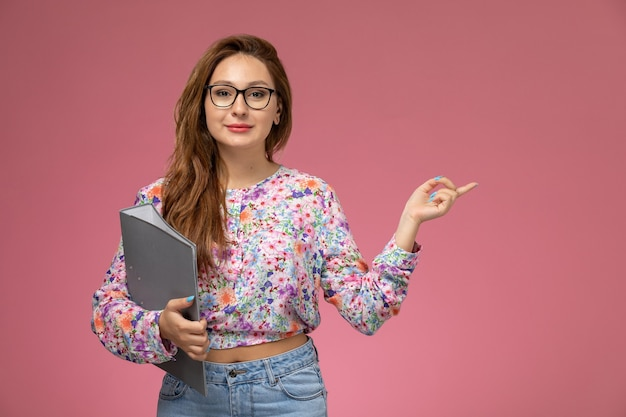 Front view young beautiful female in flower designed shirt and blue jeans holding grey files on the pink background