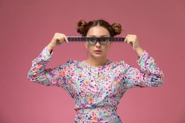Front view young beautiful female in flower designed shirt and blue jeans holding old cinema tape on the pink background