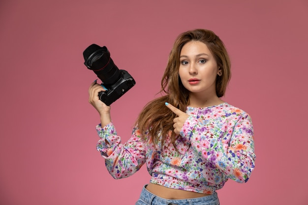 Front view young beautiful female in flower designed shirt and blue jeans holding a photo camera on pink background