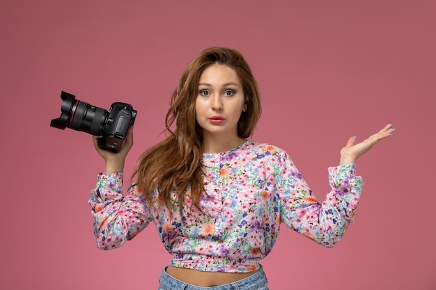 Front view young beautiful female in flower designed shirt and blue jeans holding a photo camera on the pink background