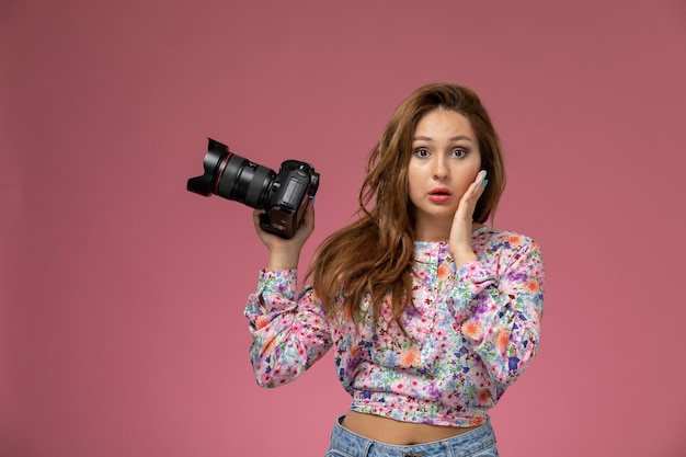 Front view young beautiful female in flower designed shirt and blue jeans holding photo camera on the pink background