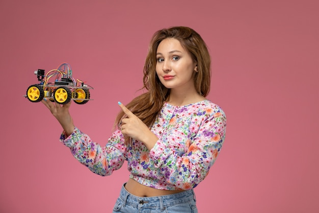 Front view young beautiful female in flower designed shirt and blue jeans holding toy car on pink background