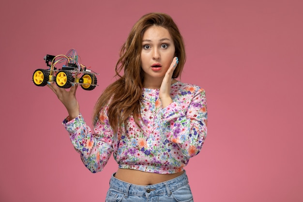 Front view young beautiful female in flower designed shirt and blue jeans holding toy car on the pink background