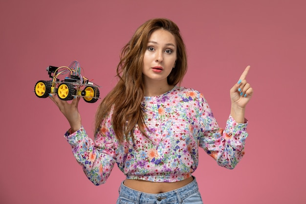 Front view young beautiful female in flower designed shirt and blue jeans holding toy car posing on pink background