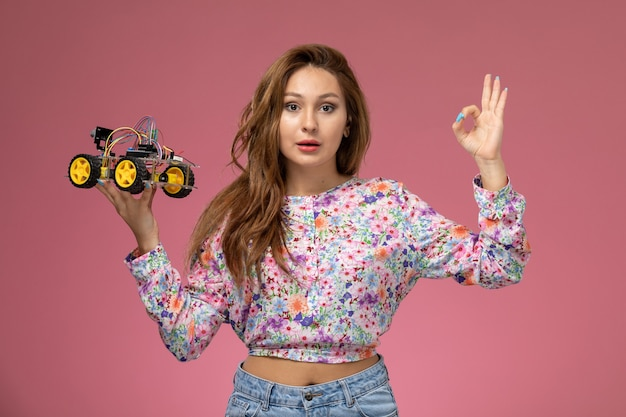 Front view young beautiful female in flower designed shirt and blue jeans holding toy car posing on the pink background